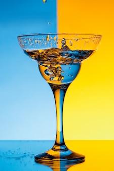 Verser de l'eau en verre sur un mur bleu et jaune