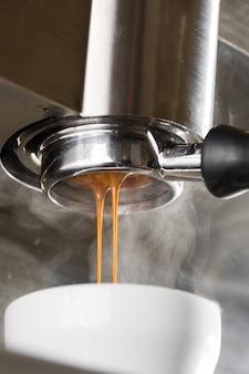 Verser le flux de café d'une machine professionnelle dans une tasse. barista en train de préparer un expresso à l'aide d'un porte-filtre. café moulu frais qui coule. boire du café noir torréfié le matin.