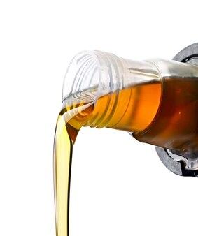 Verser des huiles synthétiques pour moteur de voiture sur une surface blanche.