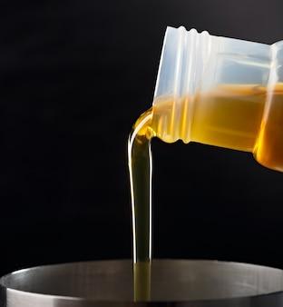 Verser des huiles synthétiques pour moteur de voiture sur une surface sombre