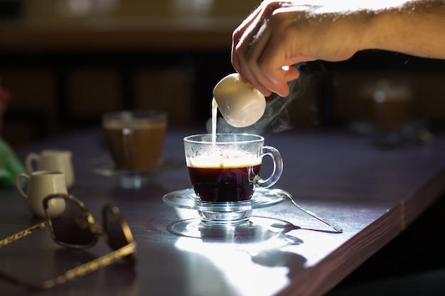 Verser le lait dans une tasse de café