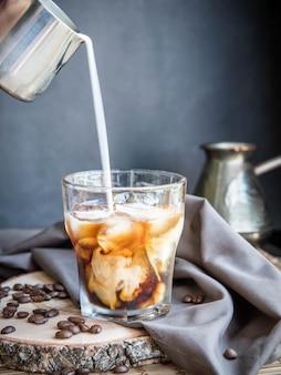 Verser le lait dans un verre de café glacé.