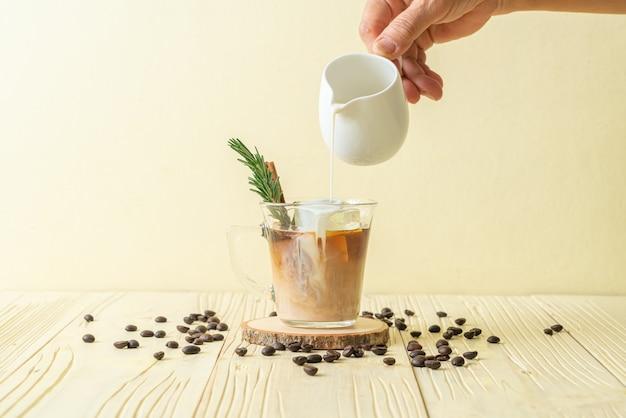 Verser le lait dans un verre à café noir avec des glaçons, de la cannelle et du romarin sur la surface du bois