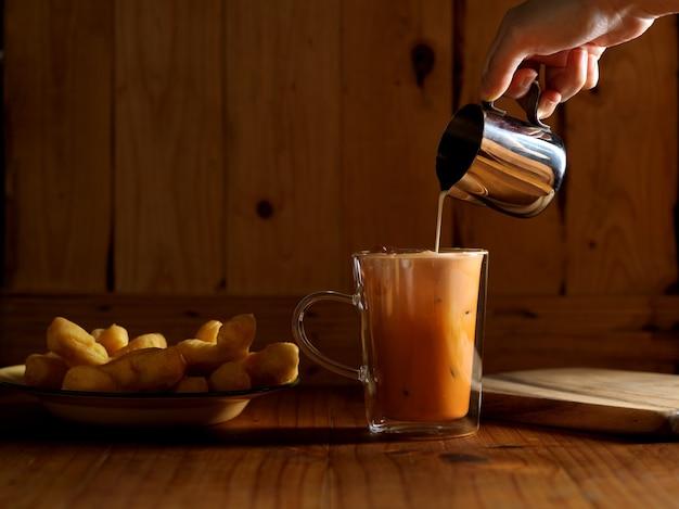 Verser le lait à la main dans du thé thaï glacé sur une table en bois avec des bâtons de pâte frits