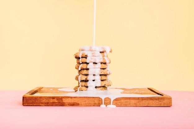 Verser le lait sur la pile de cookies sur une planche de bois