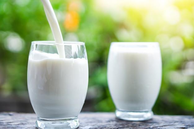 Verser le lait sur les verres à boire agrandi