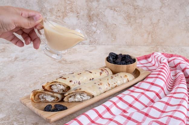 Verser à la main du lait concentré sur des crêpes maison.photo de haute qualité