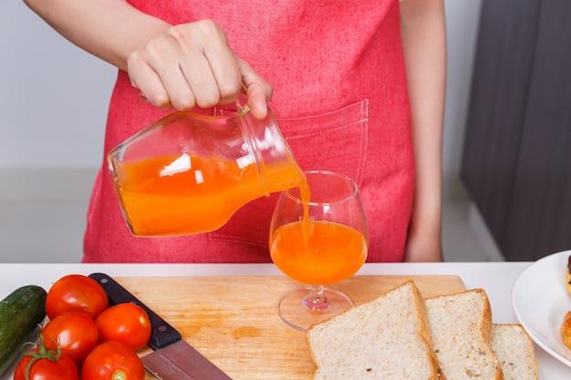 Verser à la main un jus d'orange frais dans un verre