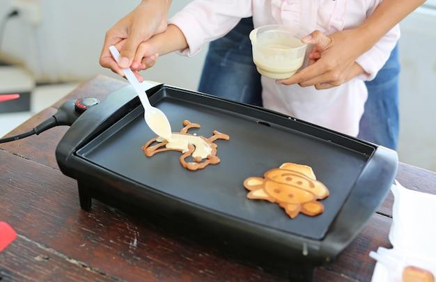 Verser le mélange de farine sur le moule pour faire une crêpe
