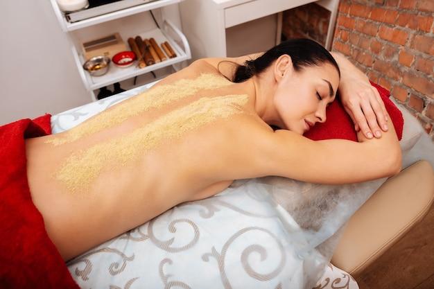 Verser la poudre de guérison. dame paisible aux cheveux noirs allongée sur une table de massage recouverte d'une serviette rouge et d'une poudre spéciale placée sur le dos