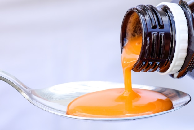 Verser le sirop antipyrétique de la bouteille à la cuillère