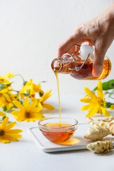 Verser le sirop de topinambour dans un bol de fleurs et de racines