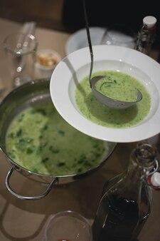 Verser la soupe crémeuse aux épinards