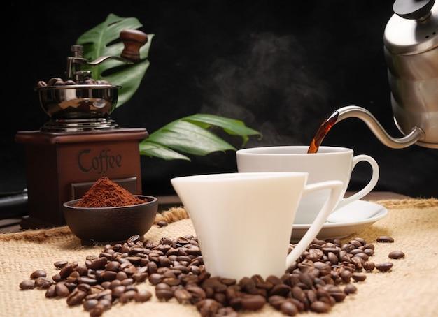 Verser des tasses à café vapeur avec moulin à café en grains torréfiés et bouilloire sur toile de jute sur la surface de la table en bois grunge