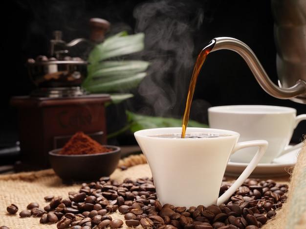 Verser des tasses à café vapeur avec moulin, grains torréfiés, café moulu et bouilloire sur toile de jute sur fond de table en bois grunge