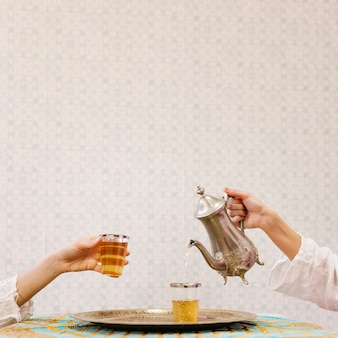 Verser le thé dans le verre à la main