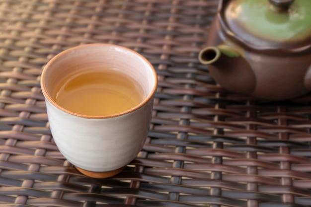 Verser une tisane chaude saine à la main dans une tasse en céramique à l'extérieur dans un café ou un restaurant