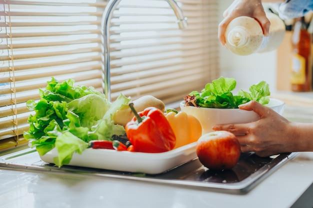 Verser la vinaigrette sur les légumes frais de la salade