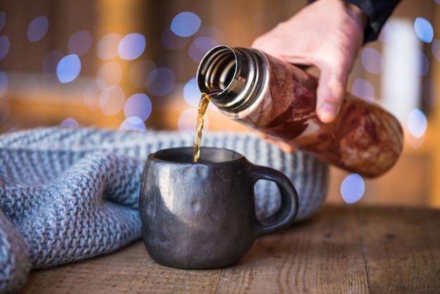 Versez le café chaud dans une tasse en céramique noire
