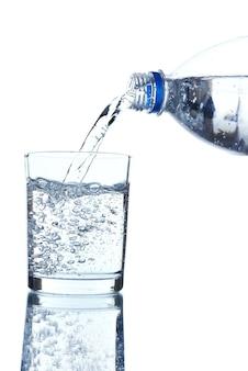 Versez l'eau de la bouteille dans le verre, sur fond bleu clair