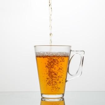 Versez le thé dans une tasse en verre.