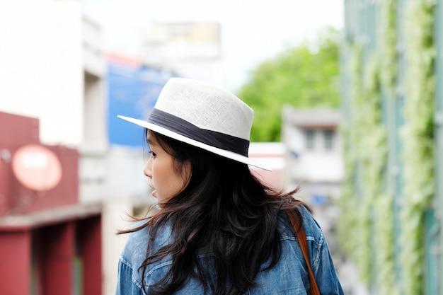 Verso du voyageur femme debout avec fond de ville en plein air, style de vie décontracté