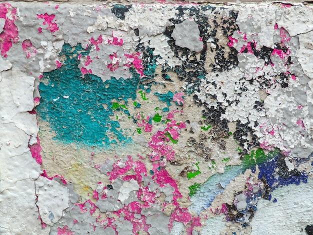 Vert, rose, peinture sur le plâtre fissuré. mur émietté avec éclaboussures de peinture multicolores