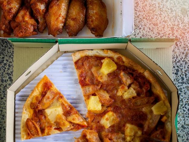 Vert vue de dessus de la pizza fine et croustillante et ailes de poulet frit dans une boîte en carton de livraison.