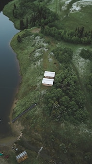 Vertical grand angle tourné de deux chalets au bord d'une jungle tropicale sur une rivière