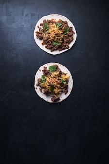 Vertical high angle shot de deux tortillas avec de la viande et du fromage fondant sur une surface noire