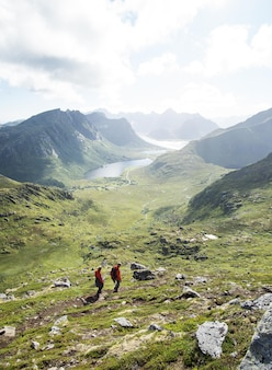 Vertical de personnes en randonnée dans les montagnes des îles lofoten par temps nuageux