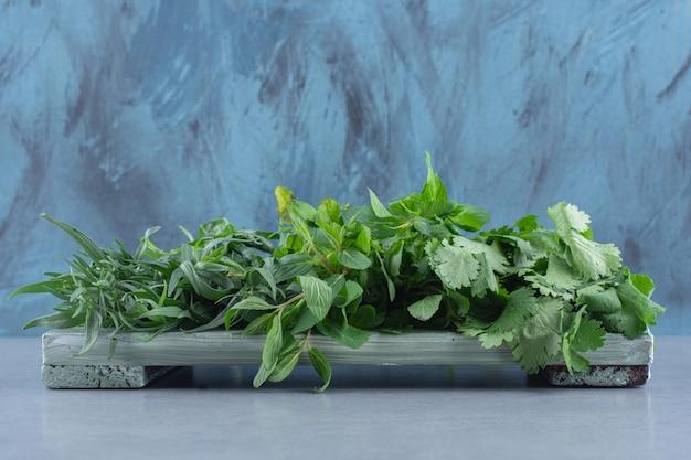 Verts frais biologiques sur planche de bois.