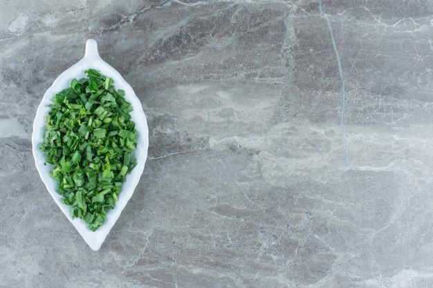 Verts râpés sur le plateau, sur la table en marbre.