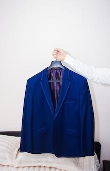 Veste bleue marié accroché sur un cintre