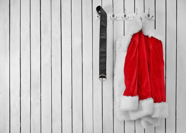 Veste et ceinture de santa sur un mur blanc en bois