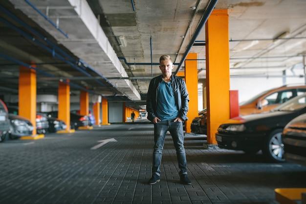 Veste en cuir bel homme est debout dans le parking et en regardant le regard confiant de la caméra, sérieux, style rock, masculin.