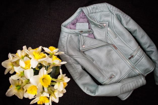Veste en cuir gris et un bouquet de jonquilles.
