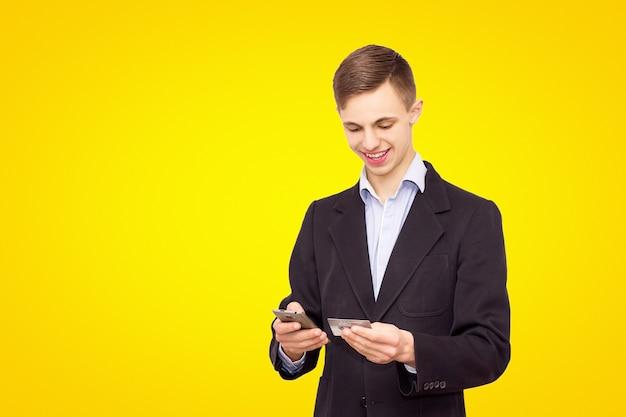 Veste de gars et chemise bleue avec téléphone et carte de crédit, isolé sur fond jaune