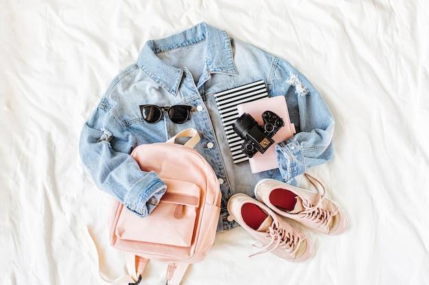 Veste en jean bleu rose pâle avec sac à dos, livre, baskets et appareil photo sur blanc. tenue élégante d'automne ou de printemps pour femmes. vêtements à la mode pour le collège. retour au concept de l'école. mise à plat, vue de dessus.