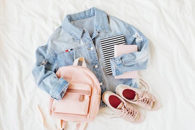 Veste en jean bleu rose pâle avec sac à dos, livre et baskets sur blanc. tenue élégante d'automne ou de printemps pour femmes. vêtements à la mode pour le collège. retour au concept de l'école. mise à plat, vue de dessus.