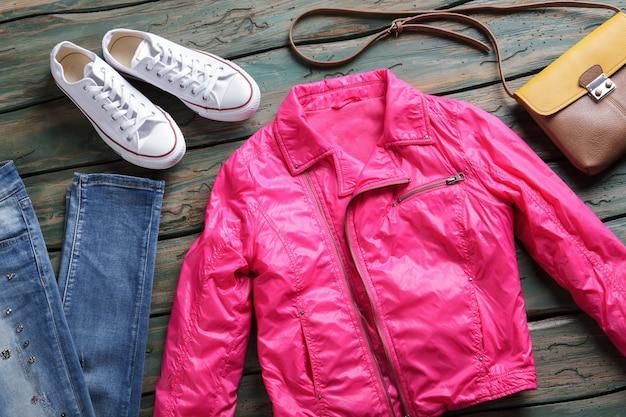 Veste rose et chaussures blanches. jean et sac bicolore marron. nouveaux vêtements d'extérieur pour fille sur étagère. veste élégante du magasin de la marque.