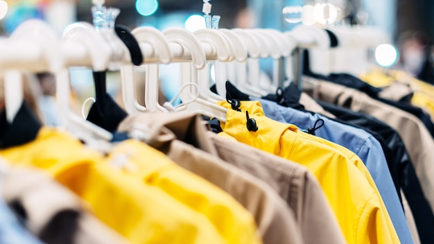 Des vestes d'été en nylon sont suspendues à des cintres dans la salle d'exposition.