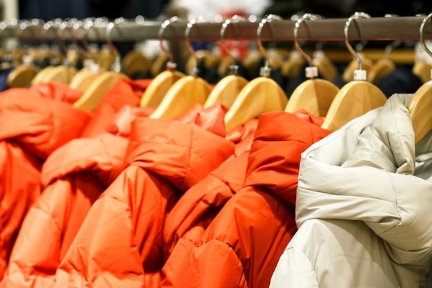 Vestes d'hiver sur un cintre dans le magasin en gros plan