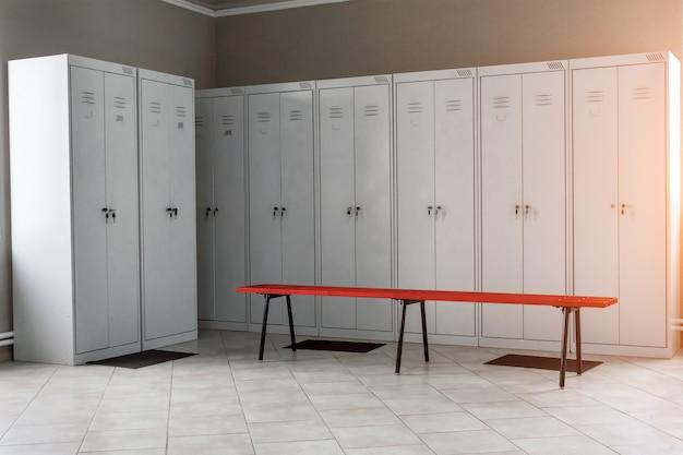 Vestiaire dans la salle de sport avec des tiroirs et des bancs en métal