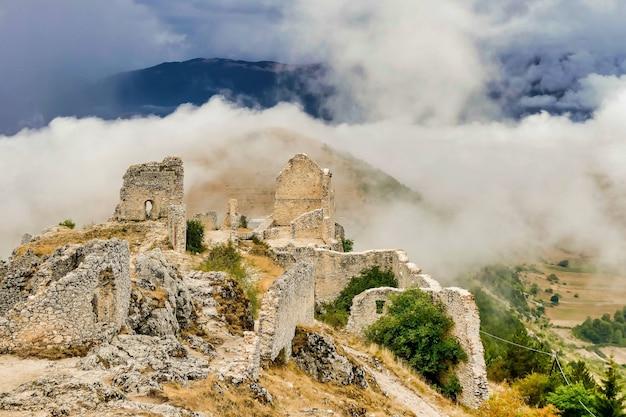 Vestiges d'un bâtiment entouré par la brume descendant des montagnes