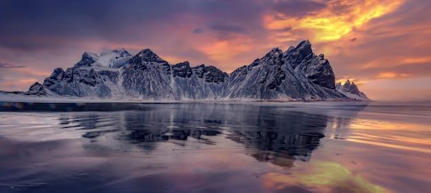 Vestrahorn mountaine sur le cap stokksnes en islande pendant le coucher du soleil avec des reflets. incroyable paysage marin de la nature islandaise. attraction touristique populaire. meilleurs lieux de voyage célèbres. image panoramique de l'islande