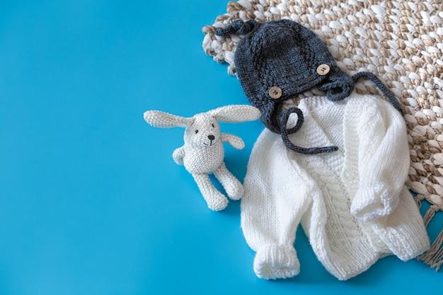 Vêtements et accessoires bébé tricotés sur fond bleu.