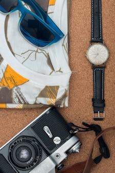 Vêtements et accessoires: chemise, lunettes de soleil, montre-bracelet et appareil photo sur parquet.