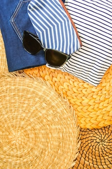 Vêtements et accessoires d'été femme sur fond de napperon en osier, vue de dessus.
