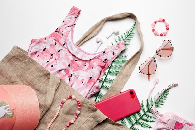 Vêtements et accessoires de fille de mode de plage sur fond blanc avec des feuilles vertes vue de dessus à plat